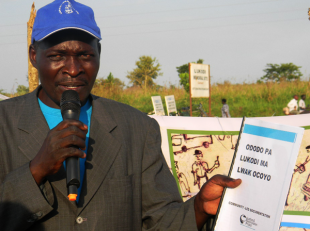 Vincent Oyet, a member of the Lukodi CORE (Community Reconciliation) Team holds a copy of 'Ododo Pa Lukodi' (the stories of Lukodi) during the launch of Community-Led Documentation in Lukodi.