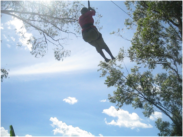 A member of the Women's Advocacy Network (WAN) soars through the air during a teambuilding retreat at a recreation center in Gulu in May 2014