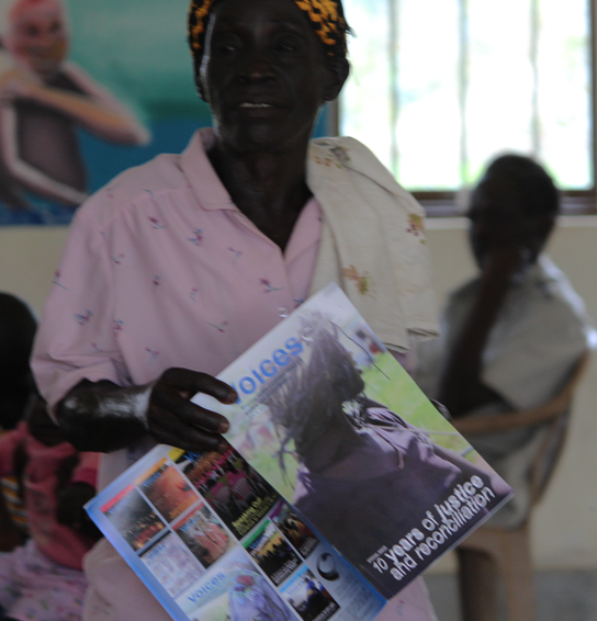 A woman holds a copy of 'Voices' in Abia, Aleptong district during the launch of a monument dedicated to the Abia massacre of 2004, on 12 December 2015.