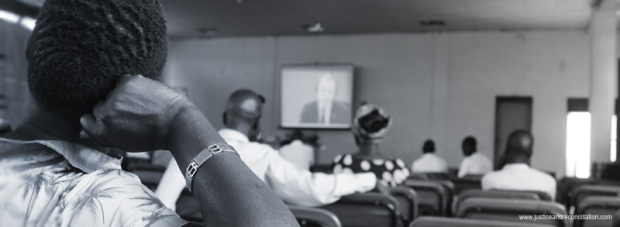 People watch a live screening of Dominic Ongwen's trial at the ICC in Gulu. Oryem Nyeko/JRP.